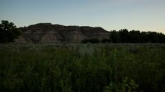 Time lapse - sunrise casts light on badlands hillside and grass Stock Footage