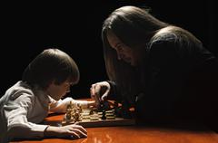 Father and son having game of chess in low key Stock Photos