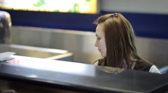 The young female is sitting in airport reception area working Stock Footage