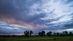 Time lapse - colorful storm clouds race away over prairie trees at suns Stock Footage