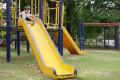 A Kid Playing on a Public Park Slide Stock Footage