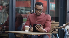 4K Portrait smiling hipster man at outdoor cafe table with computer tablet - stock footage