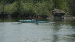 wide shot of middle aged woman kayaking on small lake - stock footage