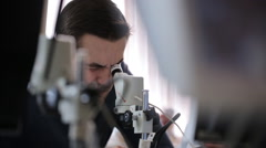 Young man screws up his eyes to look object into microscope - stock footage
