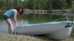 Middle aged woman kayaking on small lake - launching boat from shore Stock Footage