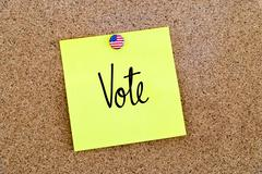 Written text Vote over yellow paper note - stock photo