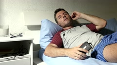 Man in bed listening to music with headphones mobile phone feeling the rhythm Stock Footage