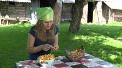 Young girl clean forest chanterelle at table village yard. 4K Stock Footage