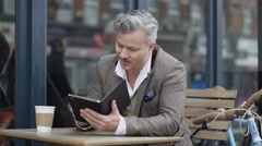 4K Portrait smiling hipster man at outdoor cafe table with computer tablet Stock Footage