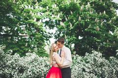 Stylish beautiful happy wedding couple kissing and embracing in Botanical Garden Stock Photos