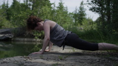 Yoga poses - woman on the rocks by a lake - tranquility scene Stock Footage