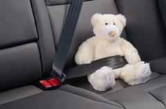 Teddy bear fastened in the back seat of a car, safety on the road Stock Photos