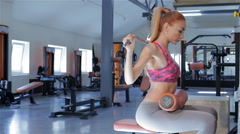 Woman trains on lat pull-down machine at the fitness centre Stock Footage