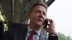 Businessman on train on his commute talking on smart phone Stock Footage