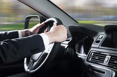 close up of young man driving car - stock photo