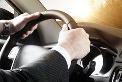 Close up of business man driving car - stock photo