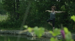 Mother doing yoga in a nature setting - stock footage