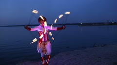 Woman fireshow performance with burning torch near river in evening Stock Footage