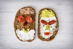 Two funny faces made of tasty bread, humorous creative food - stock photo