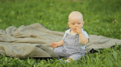 Happiness Baby boy sitting on the grass and playing on a blanket in the garden - stock footage