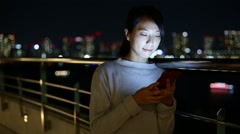 Woman using mobile phone at night Stock Footage