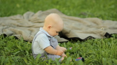 Happiness Baby boy sitting on the grass and playing on a blanket in the garden Stock Footage