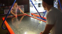 People play air hockey in the amusement park Stock Footage