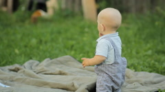 Beautiful baby boy standing on his feet and falls on ass in the garden - stock footage