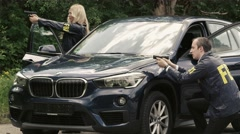Two FBII Agents Stand with pistols at their car. - stock footage