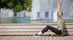 Young beautiful girl listening music and enjoy her weekend on wooden bridge Stock Footage