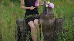 Slim girl in black dress works of flowers at sunset - stock footage