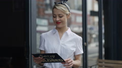 4K Smiling female cafe owner holds up a sign to show she is open for business - stock footage
