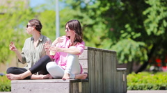 Happy young urban girls listening music in park outdoor. Caucasian tourists Stock Footage