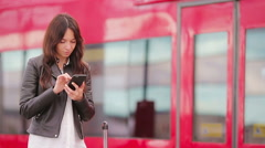 Young woman with luggage looking oh cellphone at a train station. Caucasiam Stock Footage