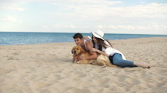 Couple in love sitting on the beach playing with dog - stock footage
