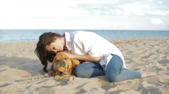 Girl playing and having fun with her dog on the beach Stock Footage