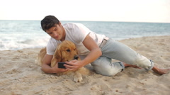 Man making with his dog on the beach - stock footage