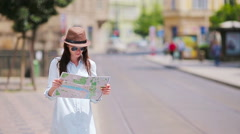 Young tourist girl with a city map searching attraction outdoors. Travel Stock Footage