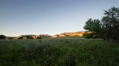 Time lapse - Sunset shadow moves up hillsides over wide meadow Stock Footage