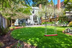 Child's swing sit in the backyard garden with well kept lawn. House exterior. - stock photo
