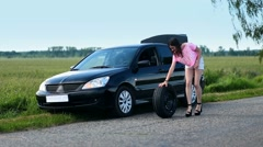 Young woman rolling spare wheel on road - stock footage