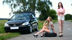 Annoyed woman sitting on spare wheel on the road - stock footage