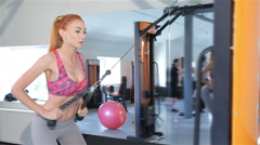 Woman pulling the rope of gym machine to her thighs at the fitness centre Stock Footage