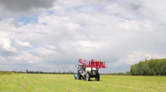 Tractor sprays a field with chemical fertilizers for agriculture Stock Footage