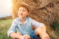 Boy sits near big haystack on the field - stock photo