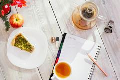Datebook, flower, cup of tea, chicken pie, apple, glass teapot and watch on Stock Photos