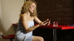 lonlely woman sitting behind the bar, drinking from glass and calling on the - stock footage