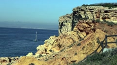 A sailing boat sails towards a boardwalk over craggy cliffs. - stock footage