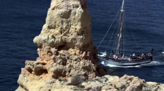 Sailing boat sails between rocks of the Atlantic coastline - stock footage