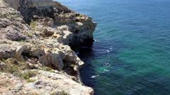 Ocean laps rocks below steep cliffs. Stock Footage